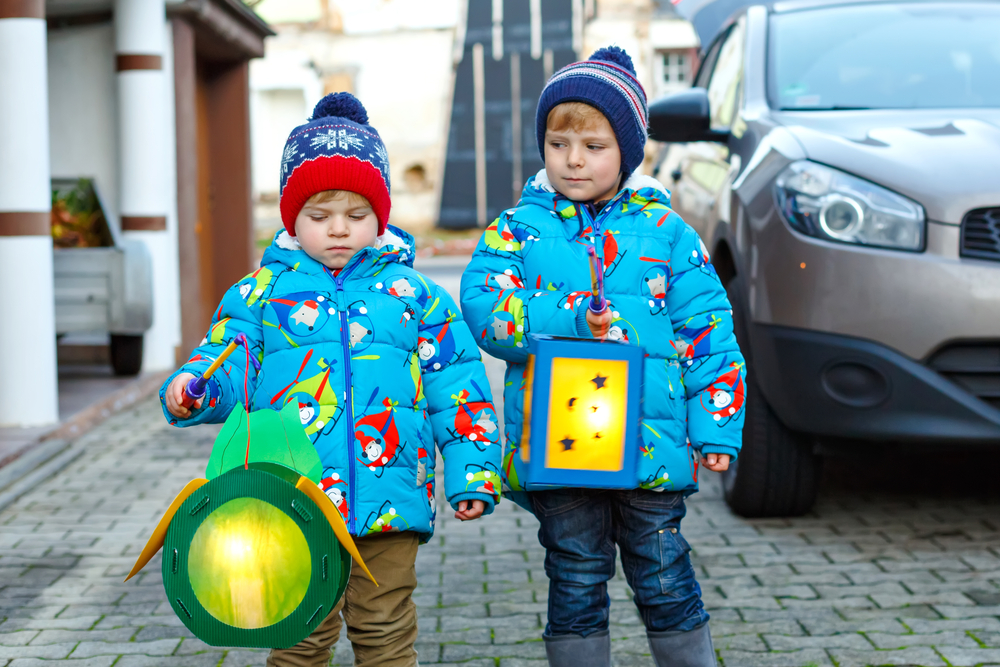 Two little kids boys holding selfmade lanterns for a Halloween or St. Martin procession. Beautiful brothers, cute siblings happy about children and family parade in kindergarten. German tradition.
